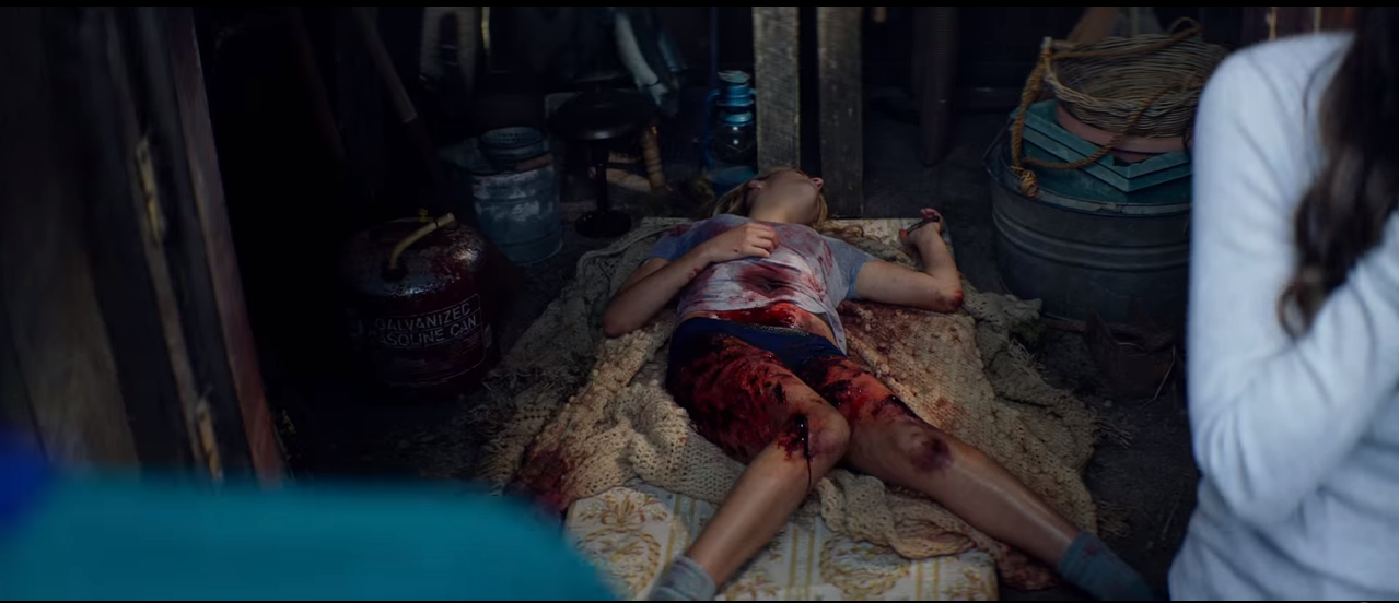 A girl covered in blood laying on the ground.